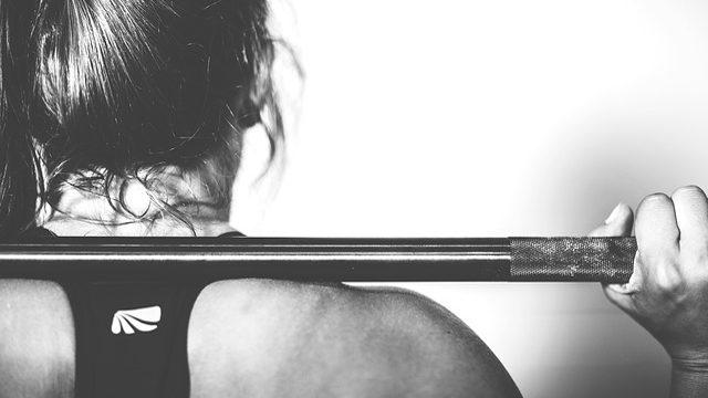 mujer sosteniendo una barra de pesas.